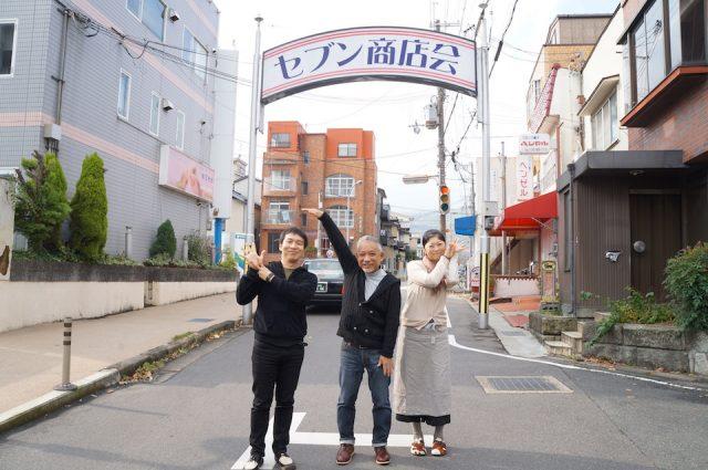 小森保人さん(左)、林定信さん(中央)、岩野しずえさん(右)。セブン商店会の西入り口にて。